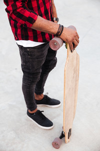 Cropped photo of young dark skinned guy holding his skateboard. Against the nature background.