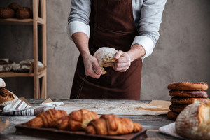 Cropped photo of young man baker standing near croissants holding bread