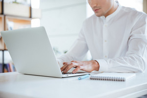 Cropped photo of young man dressed in white shirt using laptop computer. Coworking.