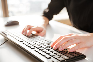 Cropped photo of young woman worker sitting in office while typing by keyboard.