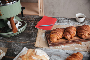 Cropped picture of a lot of pastries croissants on table near cup of coffee and notebook.