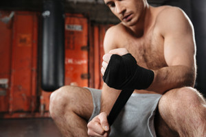 Cropped picture of concentrated man sitting in a gym. Looking at hands. Focus on hands.