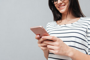 Cropped picture of happy young woman wearing eyeglasses chatting by phone over grey background. Look at phone.
