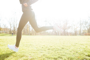 Cropped picture of woman runner in warm clothes running in autumn park early morning