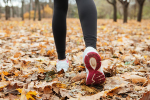 Cropped picture of young lady runner in warm clothes running in autumn park