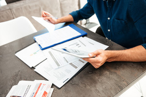 Cropped picture of young man's hands holding documents. Focus on hands with documents.