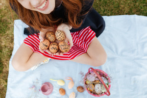 Cropped portrait of young smiling woman holding easter painted eggs while sitting with legs crossed outdoors