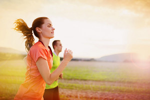 Cross-country trail running people at sunset. Runner couple exercising outside as part of healthy lifestyle.