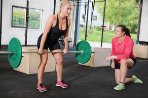Crossfit woman lifts weights with personal trainer