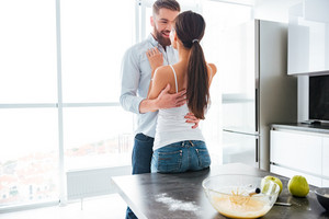 Cuddling young couple in kitchen near the table. eyes to eyes