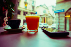 Cup of coffee, glass of juice and smartphone leaning on a table - breakfast, technology, break concept - vintage filtered technique