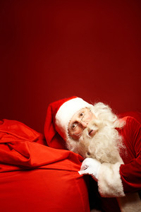 Curious Santa Claus keeping his ear by big red sack with Christmas presents