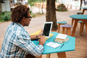 Curly arfican young man using blank screen tablet in outdoor cafe
