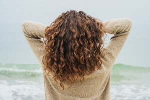 Curly brunette in a sweater on the coast faces the sea and straightens hair, view from the back