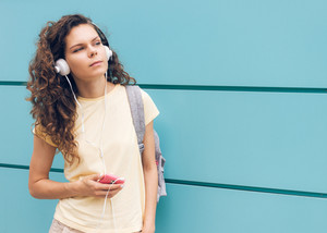 Curly brunette in a yellow T-shirt and with headphones listening to music on a background of blue wall outdoors in summer