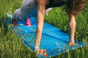 Curly slim girl doing exercises on the green meadow on the mat