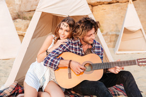 Curly young man playing guitar for his girlfriend sitting at the camping tent