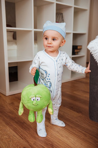 Cut little boy in hat standing and holding his toy at home