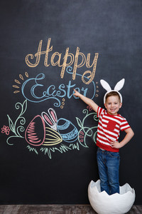 Cute adorable little boy wearing rabbit ears and standing inside big cracked eggshell pointing at chalk board with easter doodles background
