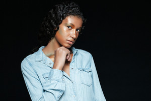 Cute african american young woman with fashion makeup in jeans shirt over black background
