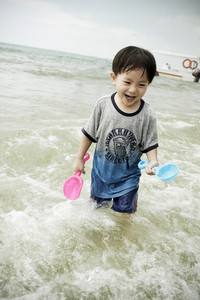 Cute asian boy playing with beach toys on tropical beach