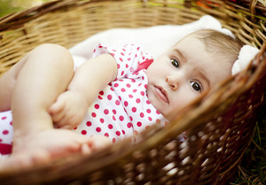 Cute baby girl lying down in basket in summer nature
