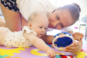 Cute baby girl playing with her caring mother