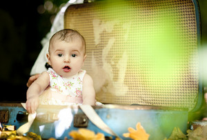 Cute baby girl sitting in old retro suitcase in summer nature