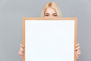 Cute blonde young woman hiding her face behind blank white board over gray background