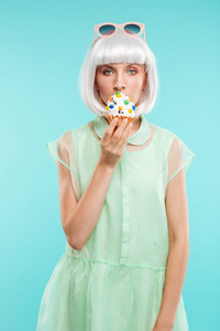 Cute blonde young woman standing and eating cupcake over blue background