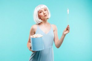 Cute blonde young woman with marshmallows holding magic stick