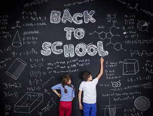 Cute boy and girl learning playfully in frot of a big blackboard. Studio shot on black background.