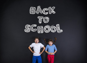 Cute boy and girl standing in frot of a big blackboard. Studio shot on black background.