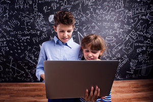Cute boy and girl with notebook at school in front of a big blackboard. Studio shot on black background.