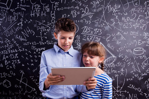 Cute boy and girl with tablet at school in front of a big blackboard. Studio shot on black background.
