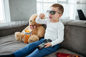 Cute boy wearing 3d glasses sitting on sofa with teddy bear at home and watching TV while eating chips. Holding remote control.