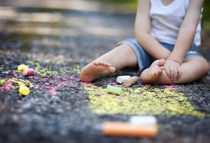 Cute child painting with vibrant chalks on the street