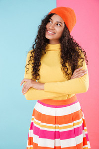 Cute curly african young woman in hat standing with arms crossed and thinking over colorful background