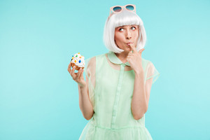 Cute funny blonde young woman standing and tasting cupcake by finger over blue background