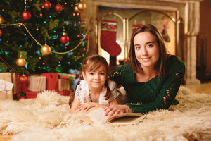 Cute girl and her mother with book looking at camera on Christmas evening