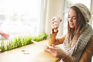 Cute girl in warm knitted clothes using touchpad in cafe