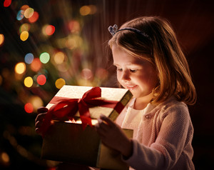 Cute girl looking into open giftbox with magic light
