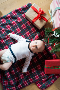 Cute little baby boy under Christmas tree lying among presents on checked blanket.