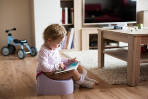 Cute little baby girl at home sitting on potty playing with tablet