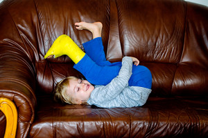 Cute little blond boy with broken leg in cast lying on leather couch, smiling, eyes closed. Child's daytime fun. Happy to be at home.