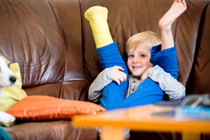 Cute little blond boy with broken leg in cast sitting on leather couch, smiling, eyes closed. Child's daytime fun. Happy to be at home.