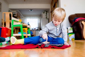 Cute little blond boy with broken leg in cast sitting on the floor in kids room, playing on tablet. Child's daytime fun. Happy to be at home.