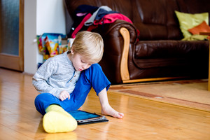 Cute little blond boy with broken leg in cast sitting on the wooden floor, playing on tablet. Child's daytime fun. Happy to be at home.