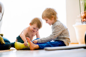 Cute little blond boy with broken leg in cast with his little brother sitting on the wooden floor, playing on tablet. Childrens daytime fun. Happy to be at home.