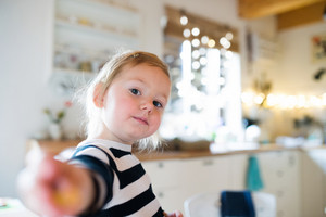 Cute little blond girl in striped dress sitting on kitchen table. Christmas season.